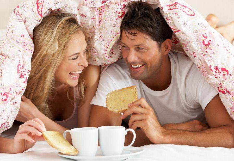 un homme et une femme prennent le petit dejeuner dans leur lit