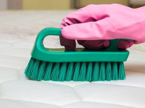 nettoyage d'un matelas à l'aide d'une brosse
