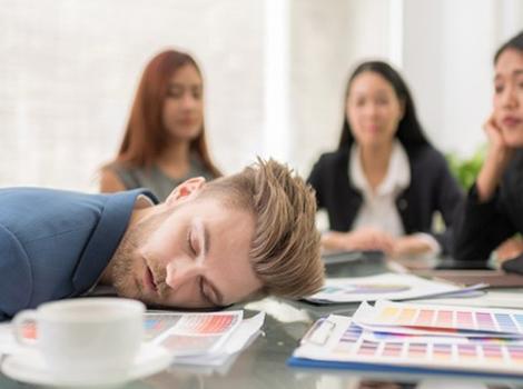 une homme  qui dort sur une table
