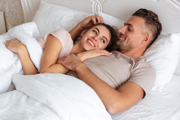 un homme et une femme qui dorment dans un lit