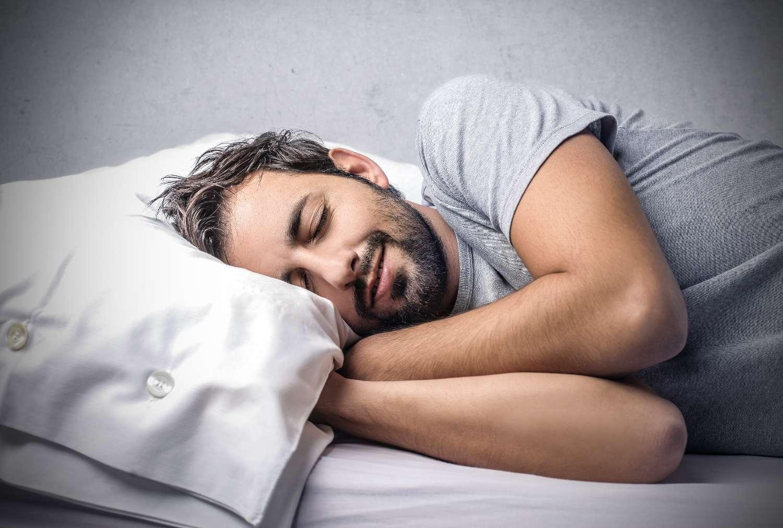 un homme qui dort dans un lit